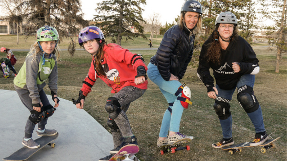Two girls and two women skateboarding