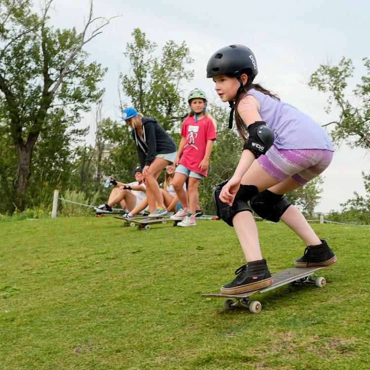 100 percent skateclub kids skateboarding on a grass hill